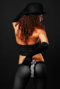 Rear view of sexy gangster hiding a handgun.